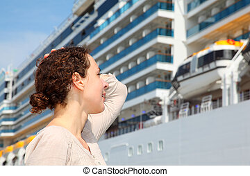 Smiling girl look at the big cruise ship and smooths hair by...