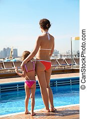 beautiful woman with her daughter standing near swimming...