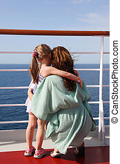 daughter and mother embracing on cruise liner deck, view from back, sunny day