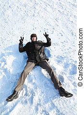 Youth lies on snow on back and shows hands gesture of victory and laughs