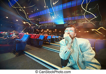 Man sits in cinema and leans chin on an elbow