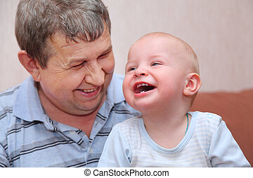 Portrait of laughing, happy old man and his grandson, focus...