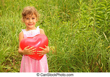 beautiful little girl in pink dress holding red balloon. Girl on nature