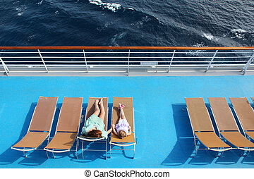 mother and daughter lying on beach armchairs on cruise liner deck, view from above