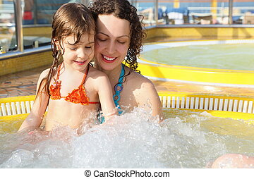 beautiful woman with her daughter is relaxing in hot tub on cruise ship.