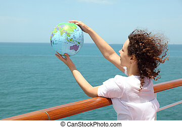 young curl woman standing on cruise liner deck and holding inflatable globe, half body, side view
