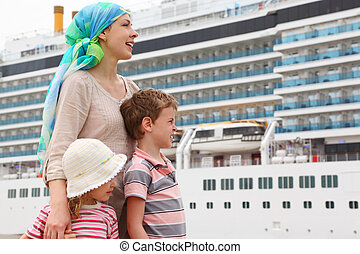 mother, son and daughter in dock, looking right, big cruise...