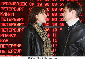 Man and woman in leather jacket standing in profile and look to each other in eyes on background of flight timetable