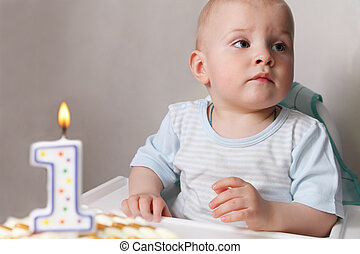 Little baby celebrating its first birthday, in front of him...