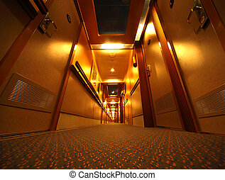 Narrow and long illuminated corridor with hotel rooms in...