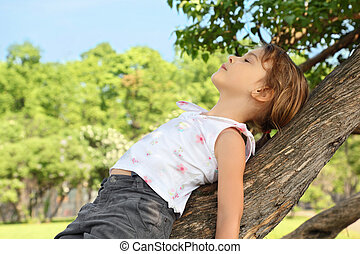 Little girl lies on caudex of tree