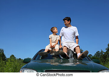 Father and son sit on roof of car in day and look on each...