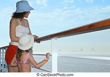 woman and her daughter standing on deck of cruise ship.