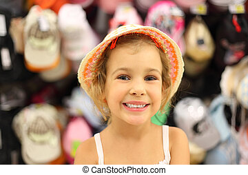 portrait of little girl trying panama in store and smiling,...