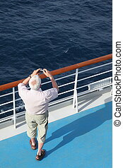 man with compact photo camera standing on deck of cruise...