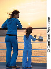 beautiful woman and her daughter both wearing tracksuits are...