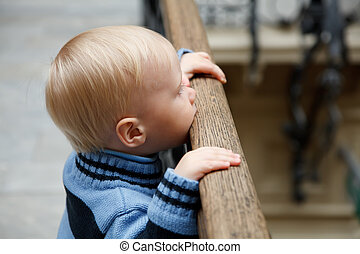 Little boy stands at fencing holding on to banister and looks downwards.