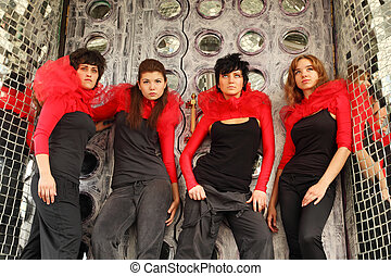 Four girls in same red-black clothes standing on place...