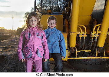 Little girl in pink clothes and boy in blue jacket standing near yellow crawler tractor