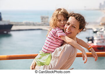 smiling beautiful woman with her daughter in focus. ships in Qaboos port in out of focus.