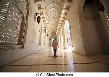 woman with kerchief walking in corridor inside Grand Mosque in Oman. Wide Angle.