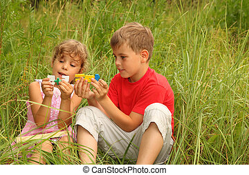 little brother and sister sitting in tall grass and play with colorful plastic numbers. 5+5 = 10. focus on numbers