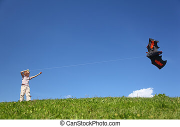 Boy in summer stands on grass and starts kite in form flittermouse