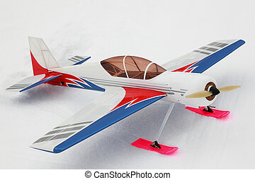 Little model of radio-controlled airplane stands on to snow