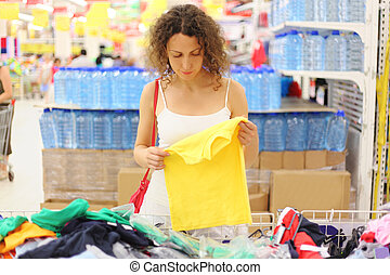 young woman in store holding yellow shirt and looking on it,...
