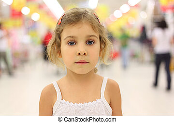 portrait of little serious girl standing in big store alone...