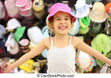 portrait of little girl trying pink panama in store and...