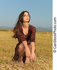 happy woman sitting on a hay stack - fashion portrait woman...