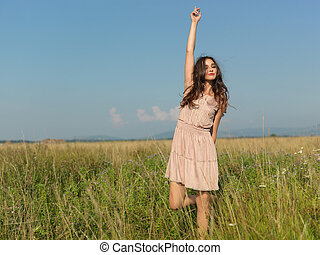happy, young woman standing in green field - beautiful young...