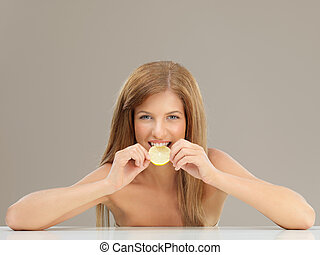 beautiful woman biting slice of lemon smiling - beauty...