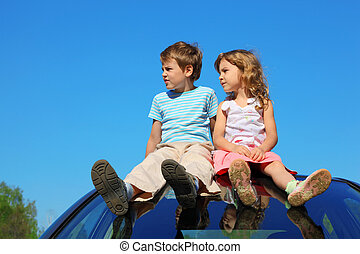 little boy and girl sitting on car roof on blue sky, looking to left side