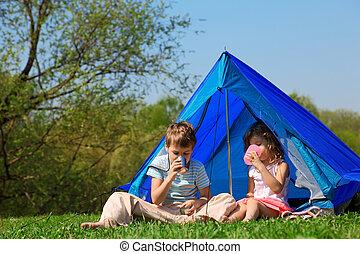 children drinking water in tent