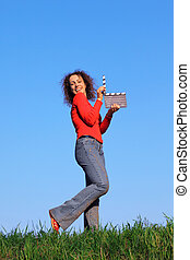 girl stands in meadow with green grass against blue sky and keeps clapperboard
