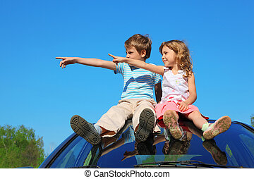 little boy and girl sitting on car roof on blue sky, looking...
