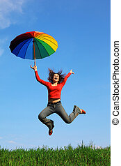 girl jumping over green grass with colorful umbrella in hand against blue sky