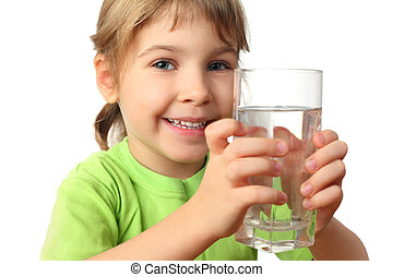 portrait of little girl in green shirt holding glass with water and smiling
