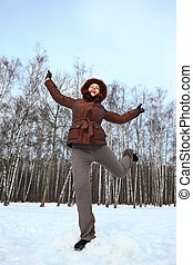 Woman stands on to snow and gravitate skyward, direct  hands and one leg upwards