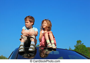 little boy and girl sitting on car roof on blue sky, hands...