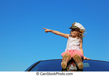 little girl sitting on car roof showing by finger on left...