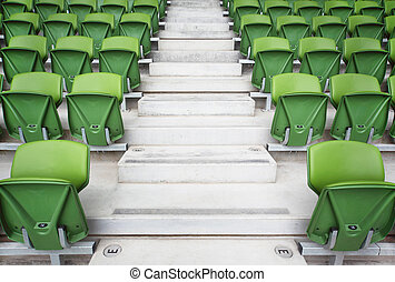 Rows of folded, green, plastic seats in very big, empty stadium. Focus on stairway