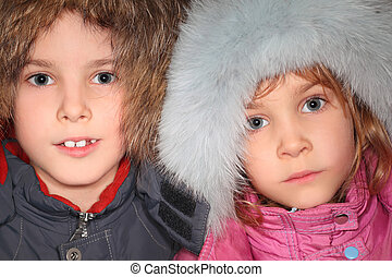 portrait of little boy and girl in big fur hoods, looking at camera