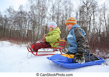 Brother and sister intend  drive from  hill in winter on sledges, focus on  brother