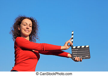 Smiling girl standing against the blue sky and keeps in his outstretched hands clapperboard