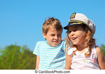 little girl with captain cap and boy at sunny day