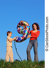 Mother and son standing in meadow with green grass on blue sky background and holding an inflatable figure of nine