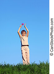Smiling boy standing field with green grass against blue sky and holds up his hands raised in rattle